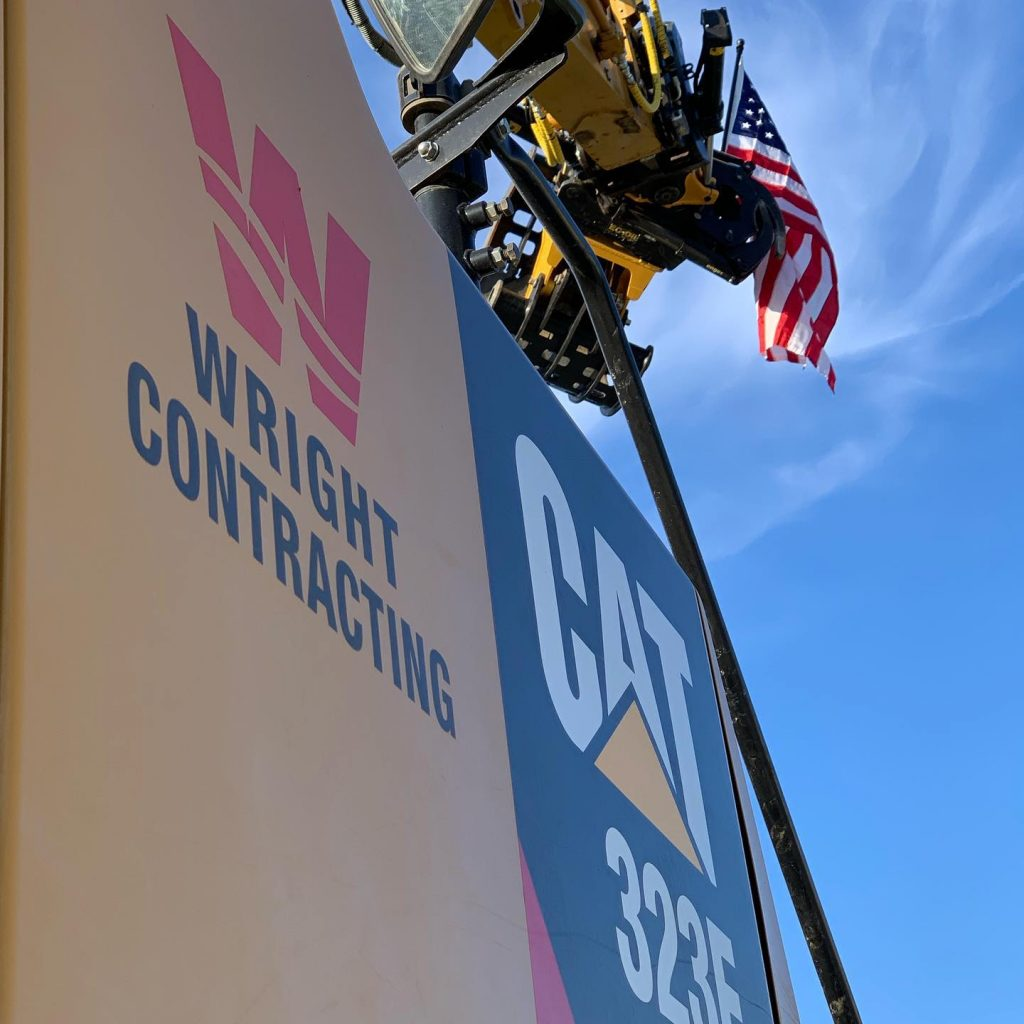 Wright Contracting Cat 3235 against a blue sky