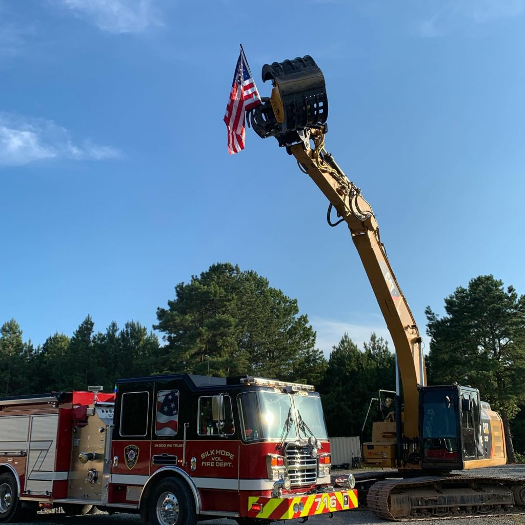 Wright Contracting Cat 3235 against a blue sky holding an American flag